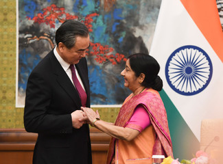 Indian Foreign Minister Sushma Swaraj shakes hands with Chinese Foreign Minister Wang Yi  as a news conference begins at the Diaoyutai State Guest House in Beijing
