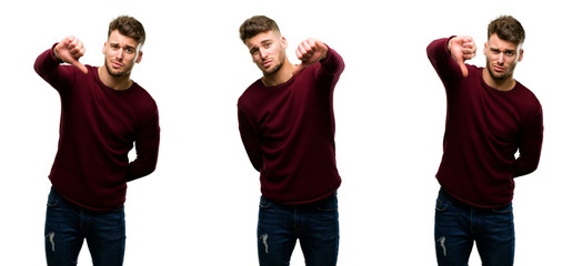 Handsome blond man showing thumbs down unhappy sign of dislike, negative expression and disapproval isolated over white background