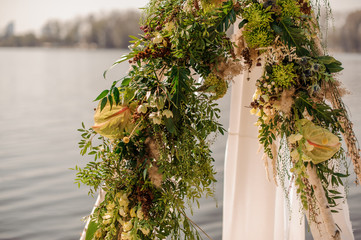 Beautiful wedding arch decorated with tropical flowers and white fabric