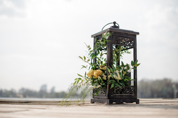 Close up iron lantern decorated with tropical flowers as a wedding decor on the river bank