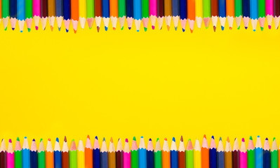 frame of colored pencils on a yellow background