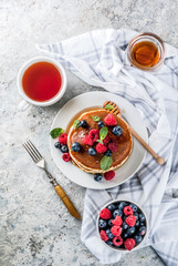 Healthy summer breakfast,homemade classic american pancakes with fresh berry and honey, morning light grey stone background copy space top view