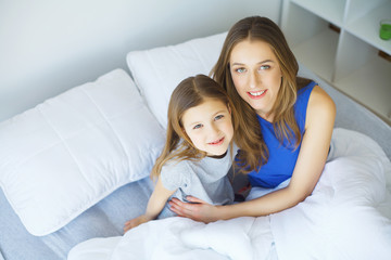 Young woman playing with little girl on bed