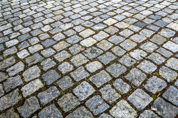 Abstract pattern of squared old-fashioned simple rough gray concrete street cobblestone pavement. Construction, decoration and background.