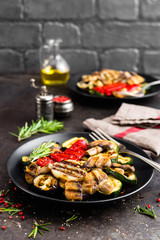 Grilled vegetable salad. Salad of barbecued zucchini, eggplant, sweet pepper, onion and mushrooms on black plate
