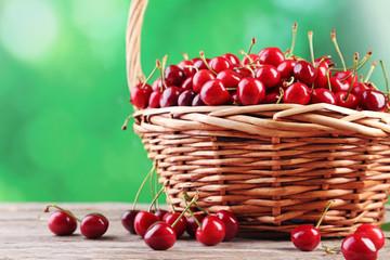 Sweet cherries in basket on wooden table