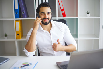 Handsome businessman sitting on his desk in the office