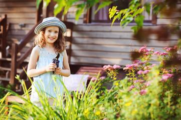 little gardener child girl helping to trim and cut spirea bush in summer garden. Seasonal yard work.
