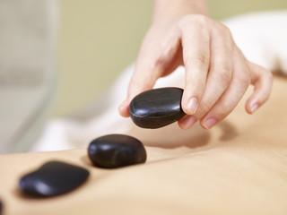 asian masseuse placing heated rock on back of female customer for hot stone massage