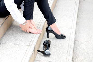 Women with leg cramps and ankles from high heels. She sat on the stairs holding her leg.