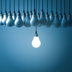 Stand out from the crowd and different creative idea concepts , One hanging light bulb glowing with unlit incandescent bulbs on dark blue background , 3D rendering.