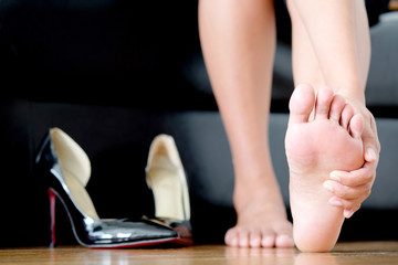 Foot Pain woman sitting  holding her feet. background shoes high heel Health concept.