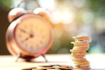 Coin pile on background clock, financial Concept saving money , investing and spending time.