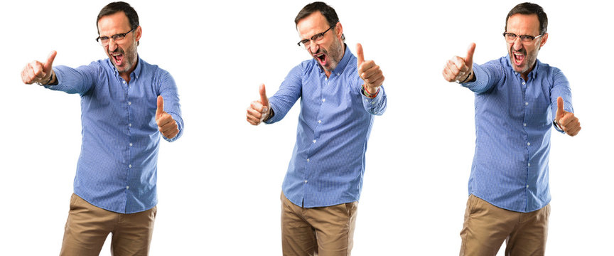 Middle age handsome man stand happy and positive with thumbs up approving with a big smile expressing okay gesture over white background
