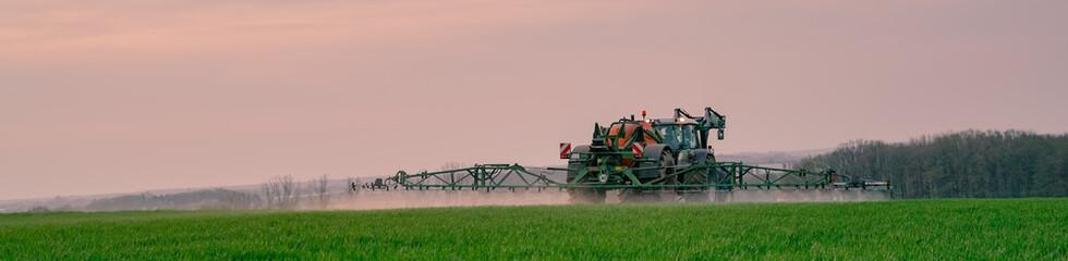 Ackerbau - Landwirt bei Pflanzenschutzmaßnahmen im Getreide am Abend, Banner