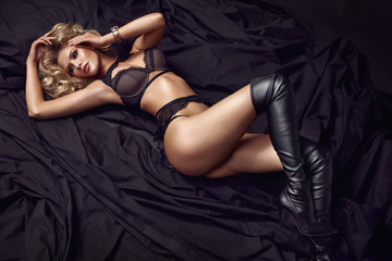 Art portrait of a sensual blonde wearing black boots