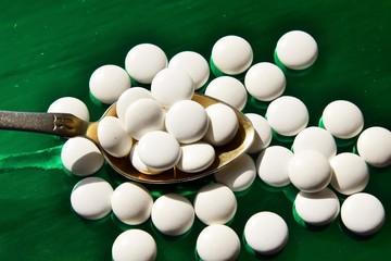 таблетки белого цвета лежат на золотой ложке на зелёном фоне