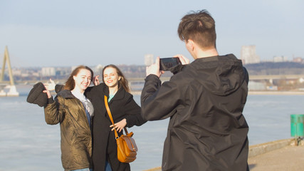 Guy takes a photo for two attractive girlfriends on the waterfront in sunny day