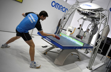 """German table tennis player Dimitrij Ovtcharov plays against robot """"Forpheus"""" in Hanover"""