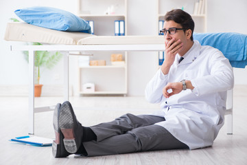 Doctor sitting on the floor in hospital