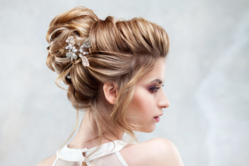 Young beautiful bride with an elegant high hairdo. Wedding hairstyle with the accessory in her hair