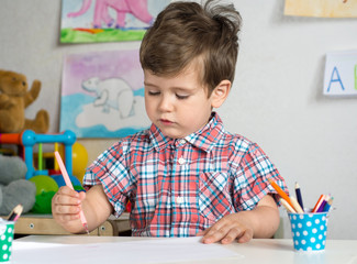 Toddler boy having fun at a daycare. Kid is painting at easel. Creative toddler, happy preschooler