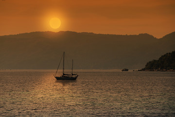 Silhouette of sailboat with sunset or sunrise background