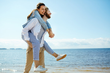 Laughing young woman embracing man while sitting on his back and enjoying summer day by seaside