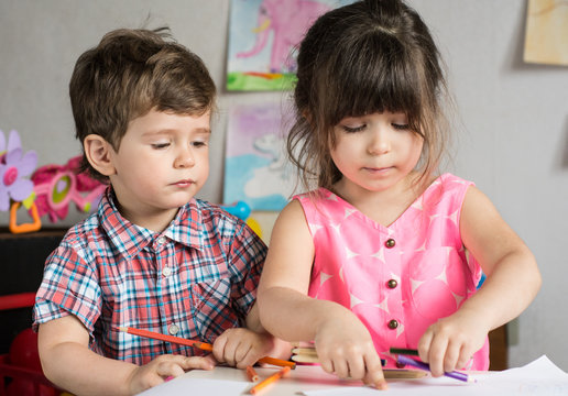 Cute kids doing their craft, painting at kindergarten or happy siblings playing at home.