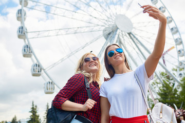 Two happy girlfriends in sunglasses and casualwear making selfie on background of enormous ferris wheel in modern theme park