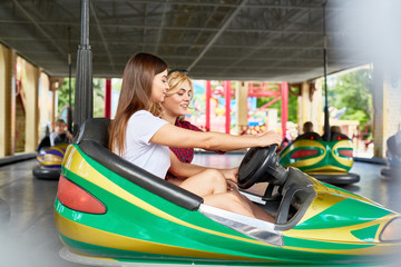 Two girls holding steer while driving car in amusement park on summer weekend or during travel to another city