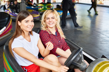 Happy girls in amusement car looking at camera while enjoying drive at leisure