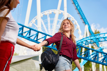 Cheerful blonde girl offering her friend to come together to one of amusements and taking her by hand