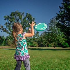 Little Girl Playing Frisbee in the Yard