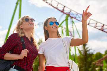 One of two girlfriends in sunglasses and casualwear pointing at amusement and saying that she would like to have fun there