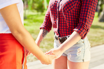 Two girlfriends in casualwear holding by hands on sunny day in park at leisure