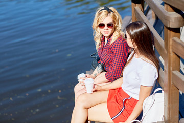 Two friendly girls with plastic glasses of coffee sitting on wooden bench by water while relaxing on sunny day in park