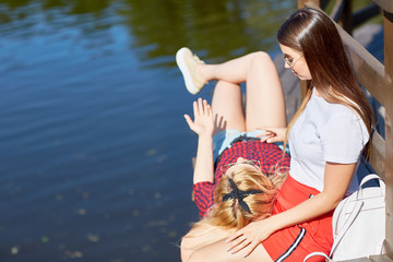 One of girlfriends lying on knees of her friend and talking about something while relaxing by water