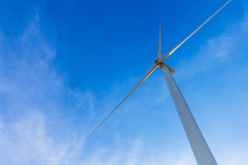 White wind turbine for alternative energy in day with blue sky background, electric clean power concept