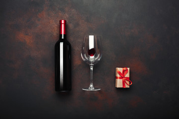 Bottle of wine gift box corkscrew and wineglass on rusty background