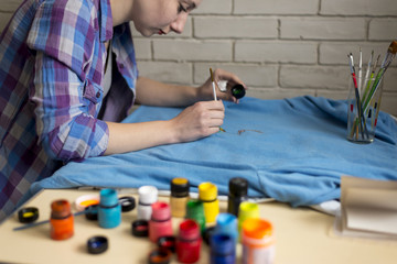 Photo of girl who drawing acrylic paints on blue clothes