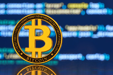 Gold coin bitcoin stacked on a bright background of business graphics close-up. Bitcoin crypto-currency. Virtual currency BTC