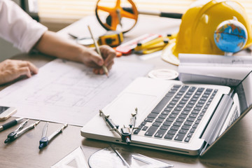 Architect hands working on blueprint plans  with  a pencil,  a ruler, calculator, smartphone, laptop and engineering tools