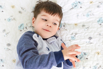 Little brunet adorable boy with appealing appearance, wears pyjamas, lies on comfortable white bed on soft bedlothes, has just awaken after sleep, plays alone. Childhood and sleeping time concept