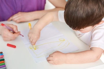 Talented small kid draws picture, has interest to art, holds colourful marker, likes to draw, her mother helps him. Little kid spends free time with making picure by himself, prepares for school