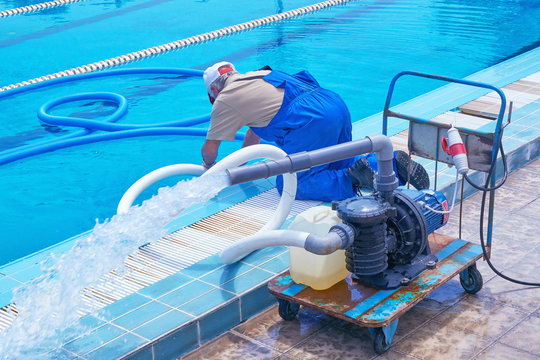 The worker in overalls makes cleaning of the sports urban pool. Cleaning systems for swimming pools. Personnel cleaning