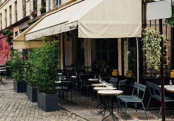 Typical view of the Parisian street with tables of brasserie (cafe) in Paris, France