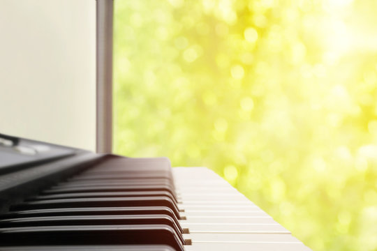 A music instrument background, music concept. A blurred warm color toned photo of electronic keyboard or piano. MIDI synthesizer piano keys near wide window, selective focus, bokeh in sunlight beams.