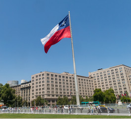 Chileans walking near the giant flag on Avenida La Alameda with the citizenship Square, in downtown Santiago de Chile. Chile.