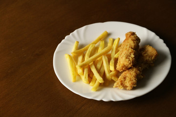 Fresh fried tasty strips chicken on the white plate on the wooden background